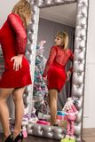 Giovane donna graziosa in vestito rosso che stending vicino allo specchio della parete Fotografia Stock Libera da Diritti