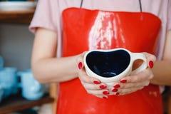 Giovane donna in grembiule rosso per terraglie che tengono la tazza a forma di del cuore immagine stock