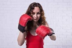 Giovane donna in guantoni da pugile rossi su un fondo bianco del mattone immagine stock