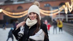 Giovane donna incantante nel parco vicino alla pista di pattinaggio sul ghiaccio fotografia stock
