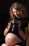 Giovane donna incinta calma con la macchina fotografica Immagini Stock
