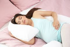 Giovane donna incinta che dorme sul cuscino di maternità Fotografie Stock Libere da Diritti