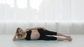 Giovane donna incinta che fa forma fisica video d archivio
