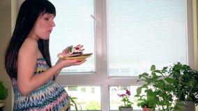 Giovane donna incinta che mangia dolce saporito che si siede vicino alla finestra a casa video d archivio