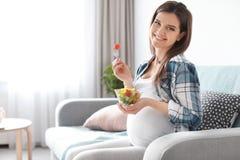 Giovane donna incinta che mangia insalata di verdure Immagini Stock Libere da Diritti