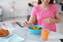Giovane donna incinta che mangia insalata di verdure Fotografia Stock Libera da Diritti