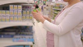 Giovane donna incinta che sceglie nutrizione del bambino nel deposito del supermercato stock footage