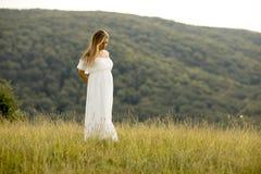 Giovane donna incinta che si rilassa fuori in natura fotografia stock libera da diritti
