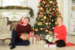 Giovane donna incinta che si siede con l'uomo e la piccola figlia vicino all'albero di Natale ed ai presente gifting fotografie stock