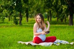 Giovane donna incinta che si siede sull'erba Immagini Stock Libere da Diritti