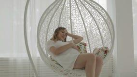 Giovane donna incinta che si siede sull'oscillazione archivi video