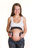 Giovane donna incinta con i trasduttori auricolari sulla pancia Fotografia Stock