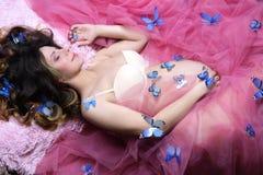 Giovane donna incinta con le farfalle sul suo corpo che si trova sulla p Fotografia Stock