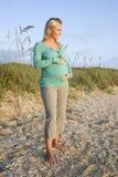 Giovane donna incinta felice che si leva in piedi sulla spiaggia fotografia stock