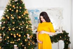 Giovane donna incinta felice in vestito giallo che si siede vicino al Chri fotografia stock libera da diritti