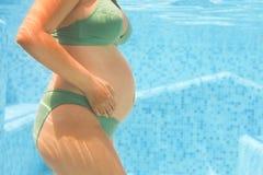 Giovane donna incinta nel nuoto verde del bikini nello stagno fotografia stock