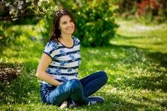 Giovane donna incinta, sedentesi in un giardino di fioritura fotografia stock