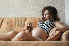Giovane donna incinta sul sofà Fotografie Stock Libere da Diritti