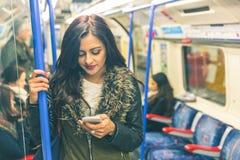 Giovane donna indiana che utilizza Smart Phone nel tubo Immagine Stock Libera da Diritti