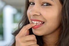Giovane donna indiana premurosa che morde il suo dito Fotografia Stock