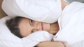 Giovane donna infastidita dai vicini rumorosi che coprono le orecchie di cuscino video d archivio