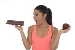 Giovane donna ispanica attraente nella frutta della mela della tenuta della cima di forma fisica e nella barra di cioccolato in s Immagini Stock