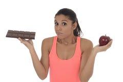 Giovane donna ispanica attraente nella frutta della mela della tenuta della cima di forma fisica e nella barra di cioccolato in s Immagine Stock