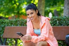 Giovane donna latina attraente felice che parla e che manda un sms sul suo Smart Phone in un parco moderno immagine stock