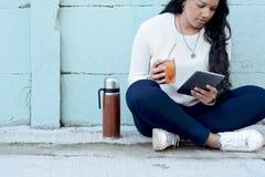 Giovane donna latina che beve il tè tradizionale dell'erba mate con la tavola fotografie stock