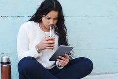 Giovane donna latina che beve il tè tradizionale dell'erba mate con la tavola immagine stock libera da diritti