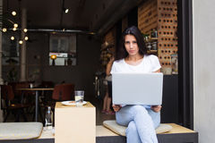 Giovane donna latina che si siede con il computer portatile aperto in caffetteria moderna nell'aria fresca Fotografia Stock