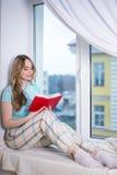 Giovane donna in libro di lettura dei pigiami dalla finestra Fotografia Stock Libera da Diritti