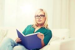 Giovane donna in libro di lettura di vetro a casa Immagini Stock