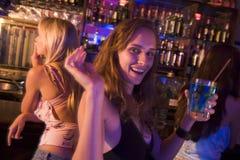Giovane donna in locale notturno che sorride e che fluttua Fotografia Stock