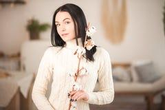 Giovane donna in maglione bianco tricottato del vestito con un ramo del primo piano del cotone Ragazza nell'interno romantico d'a fotografia stock