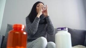 Giovane donna malata che prende le pillole con acqua stock footage