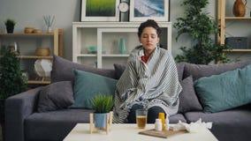 Giovane donna malata che prende temperatura corporea con il termometro in casa archivi video