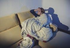 Giovane donna malata che si siede sullo strato avvolto in piumino e coperta che ritengono miseri Immagine Stock