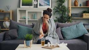 Giovane donna malata che tossisce medicina bevente che si siede sullo strato a casa video d archivio