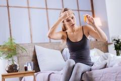 Giovane donna malata con febbre che esamina il contenitore delle pillole Fotografia Stock
