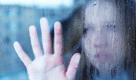 Giovane donna malinconica e triste alla finestra nella pioggia