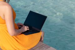Giovane donna messa su un pilastro e sul lavoro con il suo computer portatile Chiara acqua tropicale blu come fondo fotografia stock libera da diritti