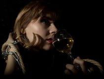 Giovane donna misteriosa con un bicchiere di vino che posa dietro il vetro trasparente coperto dalle gocce di acqua Su una priori Immagine Stock