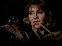 Giovane donna misteriosa con un bicchiere di vino che posa dietro il vetro trasparente coperto dalle gocce di acqua Su una priori Immagini Stock