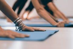 Giovane donna moderna che fa allungando gli esercizi di yoga Mani delle donne su yoga incontrata Fotografie Stock Libere da Diritti