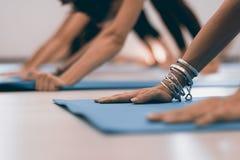 Giovane donna moderna che fa allungando gli esercizi di yoga Mani delle donne su yoga incontrata Immagine Stock