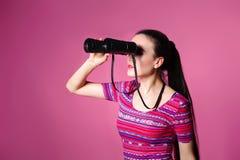 Giovane donna moderna con il binocolo a disposizione su un fondo rosa Guardando tramite il binocolo Immagini Stock