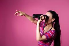 Giovane donna moderna con il binocolo a disposizione su un fondo rosa Guardando tramite il binocolo Immagini Stock Libere da Diritti