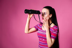 Giovane donna moderna con il binocolo a disposizione su un fondo rosa Guardando tramite il binocolo Fotografia Stock