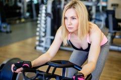 Giovane donna muscolare che risolve sulla bici di esercizio alla palestra, cardio allenamento intenso Fotografia Stock Libera da Diritti